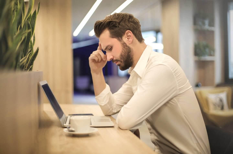 パソコンを前に考えている人の画像
